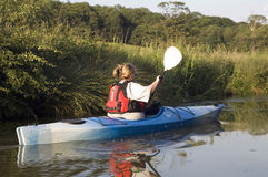 Kayaking on River. Female kayaker paddling away from the viewer Stock Image