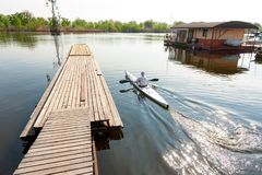 Kayaking on river while active recreation and vacation. Back view of man with paddle sitting in kayak, floating on water, and moving along the pier. Guy is royalty free stock photos