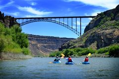 Kayaking on River in Canyon with Bridge Spaning Distance. Adventure stock photography