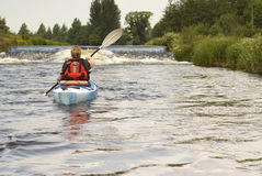 Kayaking on River Dee. Female kayaker paddling away from the viewer on River Dee in Wales - landscape orientation Stock Photo