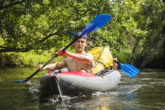 Kayaking on river. Athletic guys in canoe rowing with oars. Active recreation in nature. Water adventure. Rafting on river. Two friends in kayak with oars. Men royalty free stock images