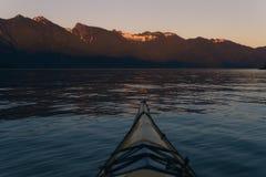 Kayaking samotnie na spokój wodzie z górami w tle podczas gdy zmierzch Fotografia Stock