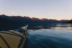 Kayaking samotnie na spokój wodzie z górami w tle podczas gdy zmierzch Obraz Stock
