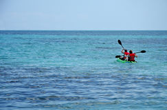 Kayaking at sea. Pair paddling into an open sea on a kayak Stock Images