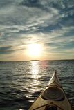 Kayaking into sunset. View from kayak, paddling across a lake royalty free stock images