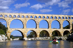 Kayaking to the Pont du Gard. Young people in a kayak reaching the Pont du Gard en France Royalty Free Stock Photography