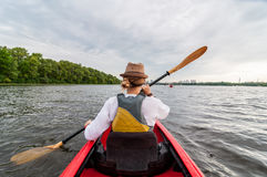 Kayaking travel. Young lady paddling the red kayak. Back view. Holiday and summer adventure.  Stock Image