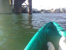 Kayaking under a bridge royalty free stock image