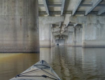 Kayaking under the bridge Stock Photo