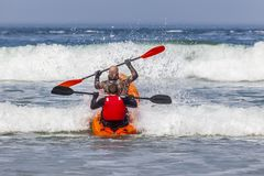 KAYAKING ON THE WAVES WITH TWO GUYS stock photography
