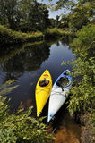 Kayaking in the wilderness. Blue and yellow kayaks on a forest river in New England Royalty Free Stock Images