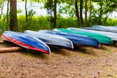 Kayakingsboten die op kust in groen bos liggen stock afbeeldingen