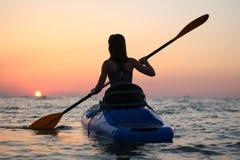 Kayakingsvrouw in kajak, Meisje die in het water van een kalme overzees roeien stock foto