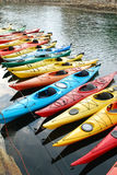 Kayaks. A row of different colored kayaks stock image
