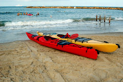 Kayaks. Red and yellow kayaks on the beach royalty free stock photography