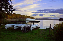 Kayaks ashore sweden lake. Sunset in Sweden landscape with kayaks ashore swedish lake Stock Photo