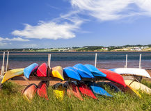 Kayaks at Atlantic shore in Prince Edward Island. Colorful kayaks stored on Atlantic shore in North Rustico, Prince Edward Island, Canada Stock Photos