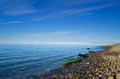 Kayaks on the bank of the White sea. The stony coast of northern White sea filled in with the bright morning sun. In the foreground - kayaks royalty free stock photo