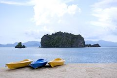 Kayaks at the Beach. Yellow and blue kayaks on a sandy beach against a backdrop of islands and the blue sea Royalty Free Stock Image