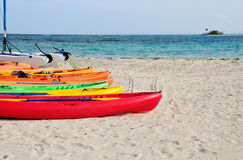 Kayaks on the beach. Colorful kayaks and sailboat on the white sand beach of Palomino Stock Images