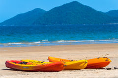 Kayaks Canoes Beach Tropics. Orange and Yellow kayak canoes lay side by side on a clear blue day on a tropical beach for hire to tourists. photo image captures Stock Photos