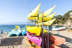 Kayaks, canoes and pedalos with slides. Girona, Spain - July 1, 2015: Kayaks, canoes and pedalos with slides on the beach of Sa Riera in Costa Brava, Catalonia royalty free stock image