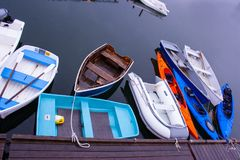 Small craft tied up dockside. These kayaks, dinghies, row boats, and small motorboats are tied up at a dock near Boothbay Harbor, Maine royalty free stock image