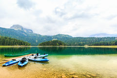 Kayaks docked on the shore of Black Lake, Durmitor National Park, Zabljak, Montenegro. Sea kayaks boats docked on the shore of Black Lake. Mountain landscape at royalty free stock photos
