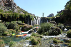 Kayaks down the river. Kayaks floating down river beyond waterfall Stock Photography