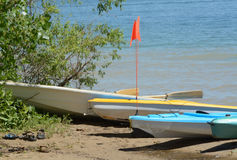 Kayaks et bateaux sur le rivage du lac Images libres de droits