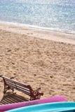 Kayaks et un banc sur la plage Image libre de droits