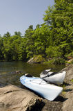 Kayaks on an Island. Two kayak on the shoreline of a northern lake in mid July Royalty Free Stock Images