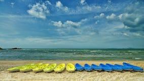 Kayaks jaunes et bleus sur une plage typique Photographie stock libre de droits