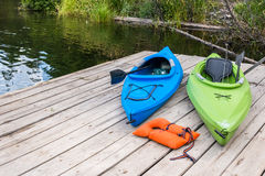 Kayaks and Life Jacket on Dock. Two colorful kayaks with life jacket and fishing gear lying on wooden pier stock photography