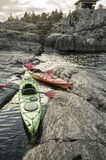 Kayaks are moored on the rocky shore, in the background you can Stock Images