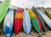Kayaks in Mousehole. Mousehole, England - April 28, 2017: Harbor of Mousehole with kayaks against a great stone wall of the quay, Cornwall Royalty Free Stock Photos