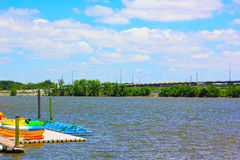 Kayaks and pedal boats on a sunny day. Stock Photos