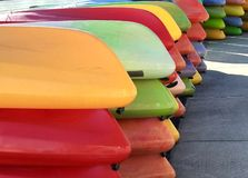 Kayaks piled in colorful rows royalty free stock images