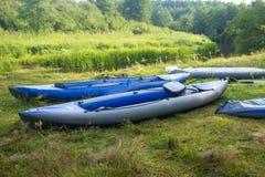 Kayaks pour transporter le long par radeau de la rivière sur la berge Bateaux ou canoës sur le rivage de rivière photos libres de droits