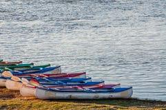 Kayaks on River Bank Stock Photography