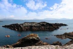 Kayaks among rocky islands Stock Photos