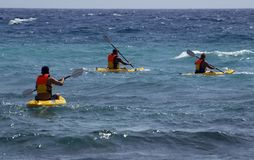 Kayaks at sea. Three kayaks in the stormy ocean royalty free stock photography