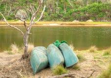 Kayaks on the shore of an Australian river. Three kayaks on the shore of a river in the Australian bush Stock Image