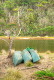 Kayaks on the shore of an Australian river. Three kayaks on the shore of a river in the Australian bush Stock Images