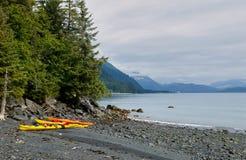 Kayaks on shore of Prince William Sound, USA. Kayaks on shore of Prince William Sound against mountains, Alaska, USA Royalty Free Stock Images