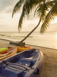 Beach Sunrise With Kayaks. Kayaks sitting on the beach at dawn with a beautiful sunrise Stock Images