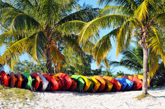 Kayaks Stacked on Beach. Sea Kayaks Stacked on Beach Under Palm Trees Royalty Free Stock Photos