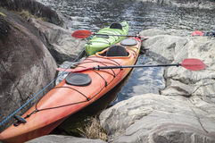 Kayaks stand moored on a rocky seashore. Stock Photo