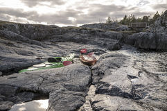 Kayaks stand moored on a rocky shore, in the background there is Stock Photo