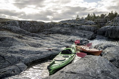 Kayaks stand moored on a rocky shore, in the background there is Royalty Free Stock Images